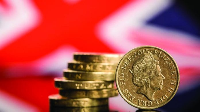 A stack of British one pound sterling coins stands in front of a British Union flag in this arranged photograph in the United Kingdom, on June 13, 2016.
