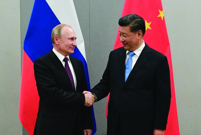 Russian President Vladimir Putin shakes hands with Chinese President Xi Jinping during their meeting on the sideline of the 11th edition of the BRICS Summit, in Brasilia, Brazil November 13, 2019.