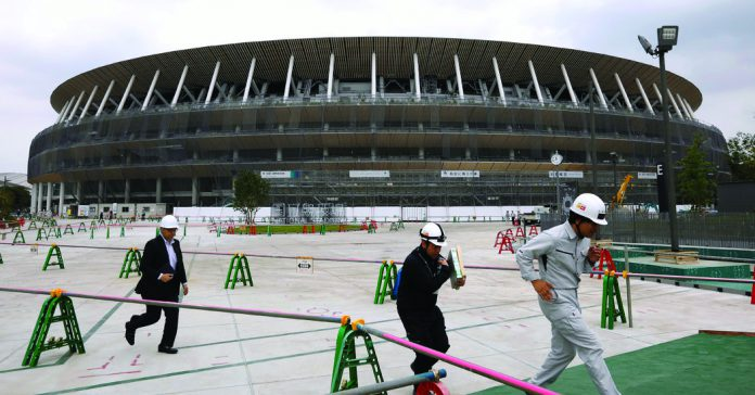 Workers at the construction site of the New National Stadium, a main venue of the 2020 Tokyo Olympic.