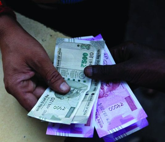 A customer hands Indian currency notes to an attendant at a fuel station in Mumbai, August 13, 2018.